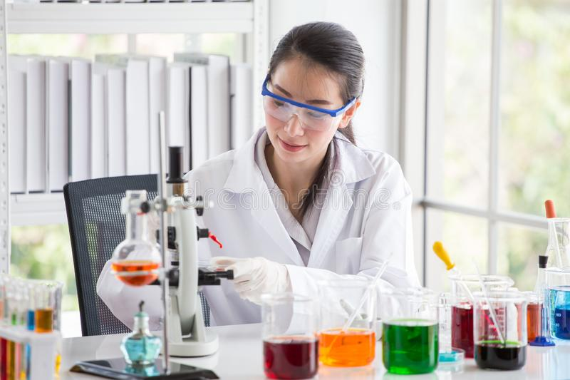 Asian woman Scientist Research and Reaction woman pouring a liquid in a tube in Laboratory , science biology medicine chemistry. Concept, microscope, analysis stock photos