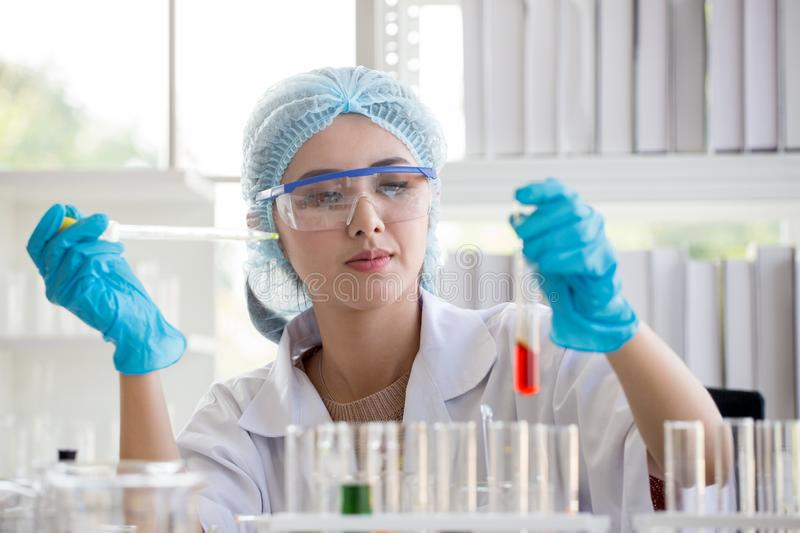 asian woman Scientist Research and Reaction woman pouring a liquid in a tube in Laboratory , science biology medicine chemistry royalty free stock images