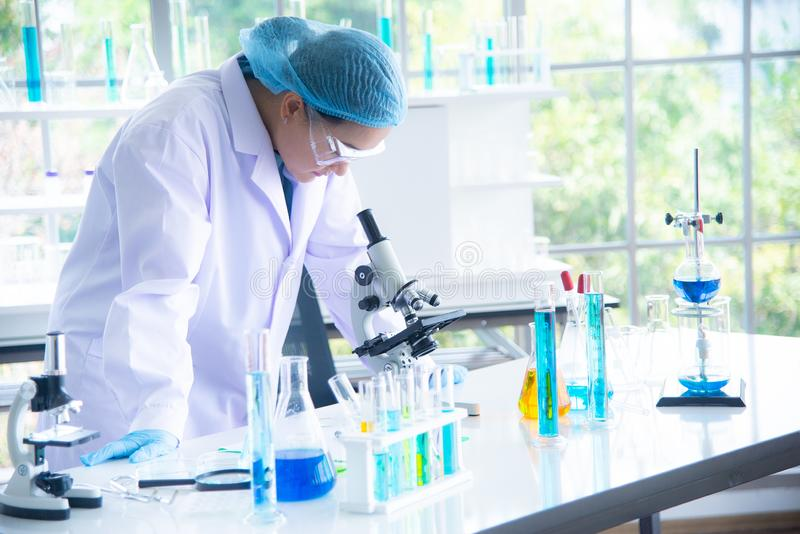 Asian woman scientist, researcher, technician, or student conducted research or experiment by using microscope which is scientific royalty free stock image