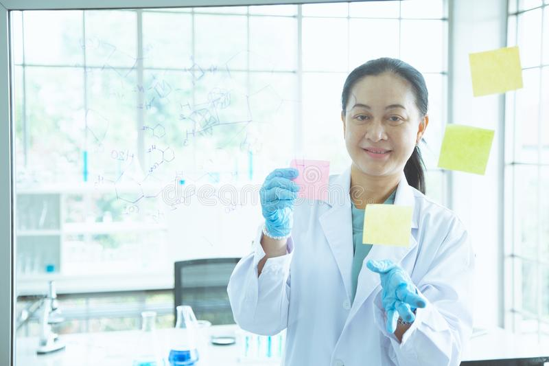 Asian woman scientist stick colorful short note on the board stock images