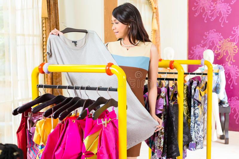 Asian woman shopping in fashion store stock image