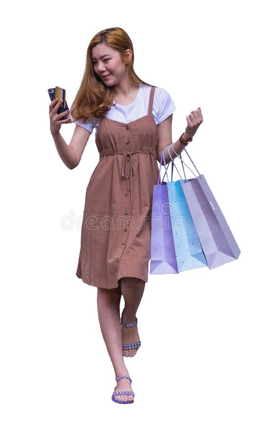 Asian woman shopping holding shopping bag and use of mobile phone and credit or debit card isolated on white background. stock photos