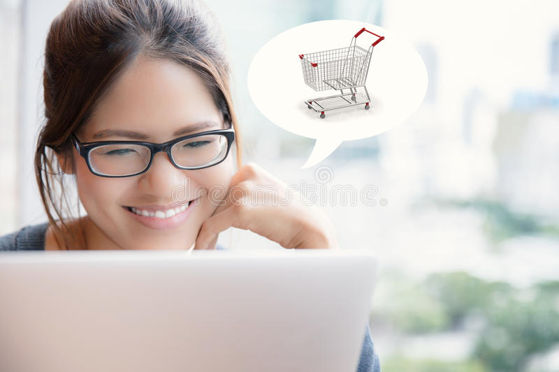 Asian woman shopping online. With shopping cart stock images