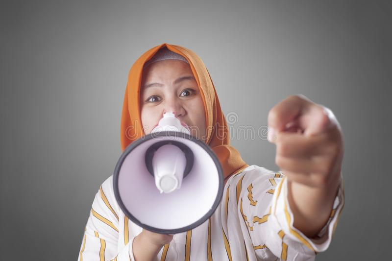 Asian woman Shouting with Megaphone. Young Asian woman wearing hijab shouting with megaphone and pointing to camera with selective focus. Leader or supporter stock photo