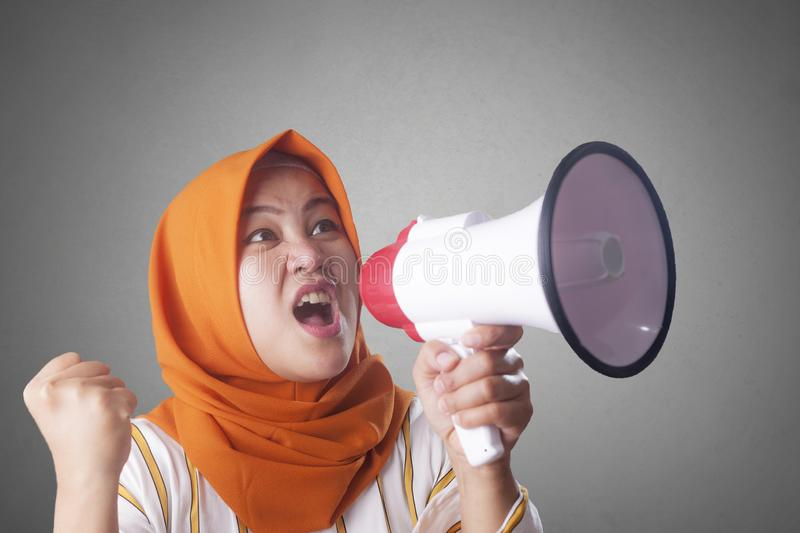 Asian woman Shouting with Megaphone. Young Asian woman wearing hijab shouting with megaphone and pointing to camera. Leader or supporter concept. Close up body royalty free stock images