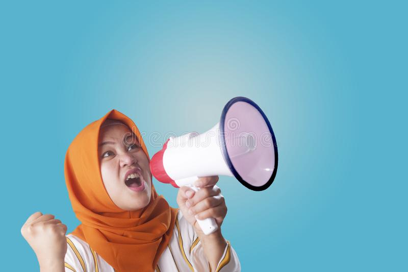 Asian woman Shouting with Megaphone. Young Asian woman wearing hijab shouting with megaphone and pointing to camera. Leader or supporter concept. Close up body stock photos