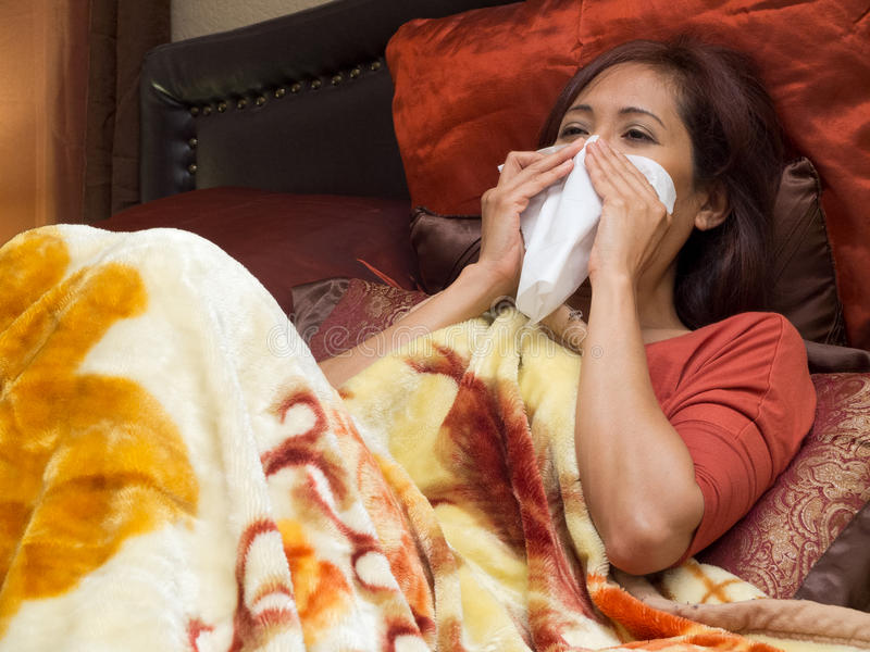 Asian woman sick of colds. Woman sick of Colds on bed stock photography