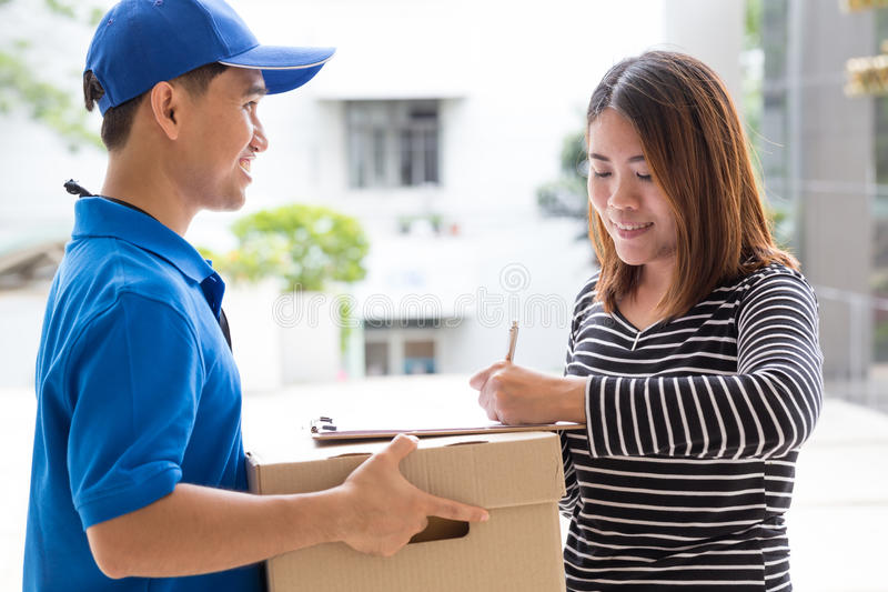 Asian woman signing receipt of delivered package. Asian women signing receipt of delivered package at home stock image