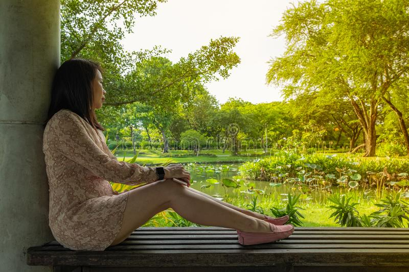 Asian woman sit on a bench against concrete pillar. Be abstracted looking at the outside garden as a backdrop royalty free stock photos