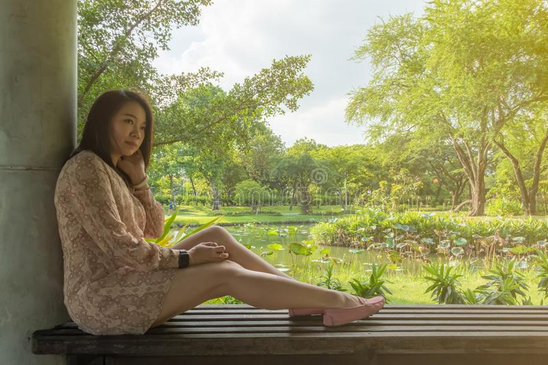 Asian woman sit on a bench against concrete pillar. Be abstracted, there are beautiful garden as background royalty free stock images