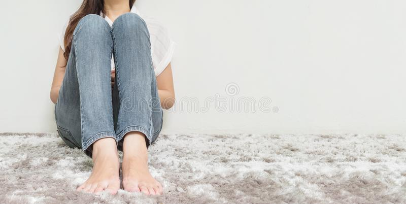 Asian woman sit on gray carpet floor with white cement textured background at the corner of house with copy space. Closeup woman sit on gray carpet floor with royalty free stock photos