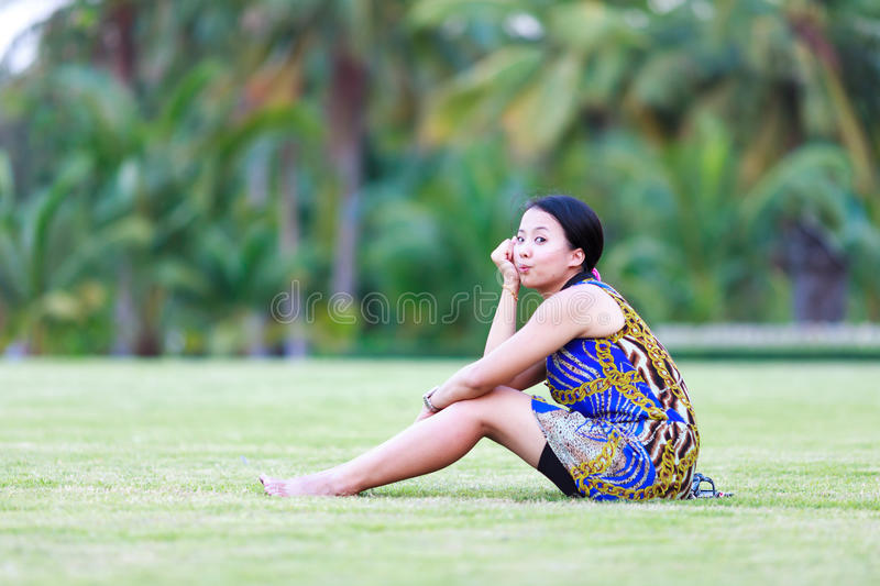Asian woman sit on ground in park stock images