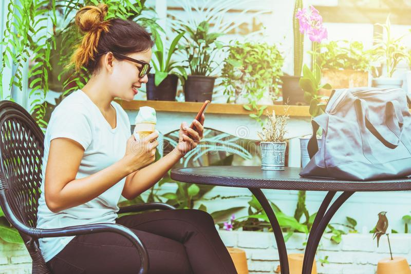 Asian woman sit relax. Hands are holding the phone. In the coffee shop.  royalty free stock photography