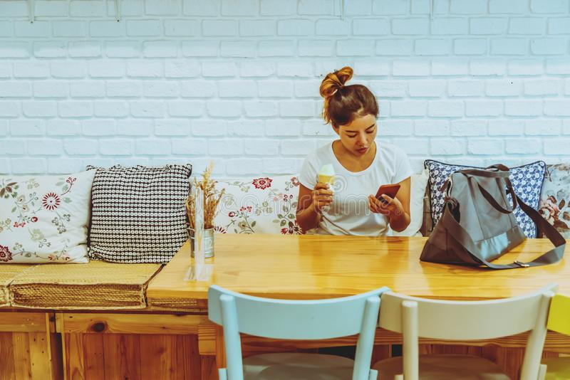 Asian woman sit relax. Hands are holding the phone. In the coffee shop. Girl travel nature in the holiday stock photos
