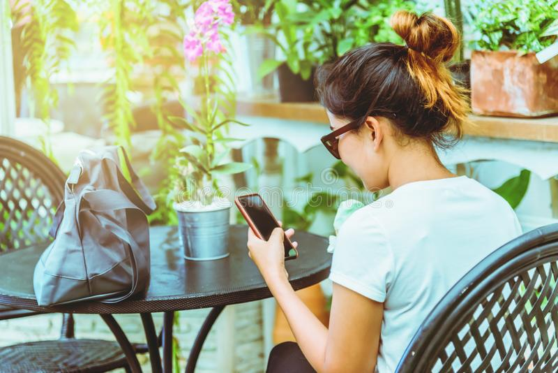 Asian woman sit relax. Hands are holding the phone. In the coffee shop royalty free stock image