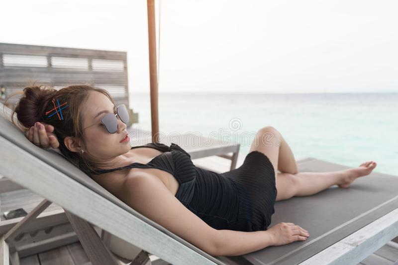 Asian woman sitting on bedchair beach royalty free stock images