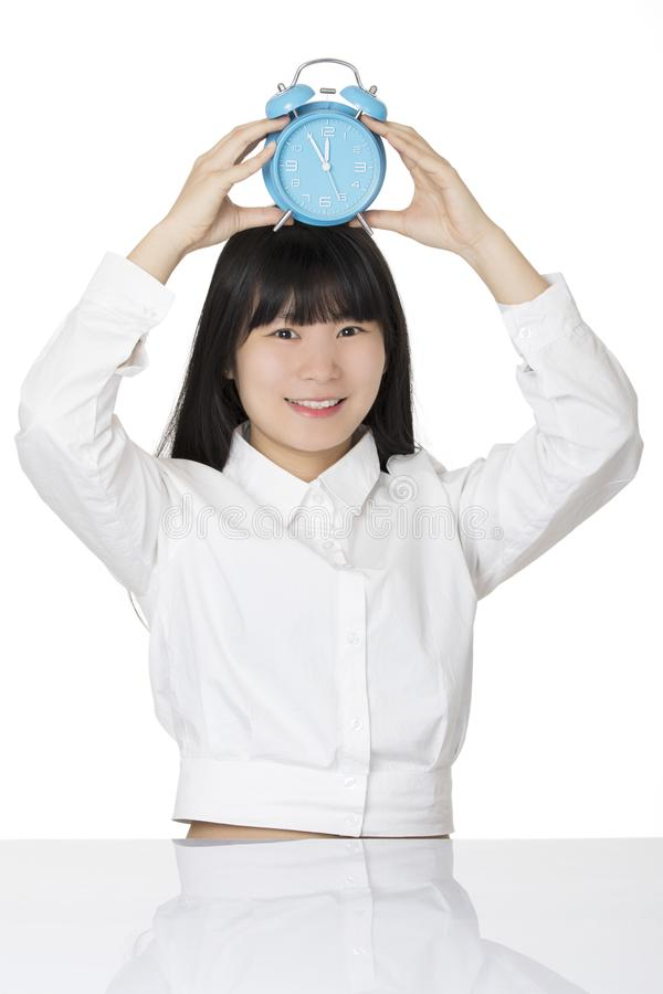 Asian woman sitting at desk smiling with a clock isolated on wh stock photography