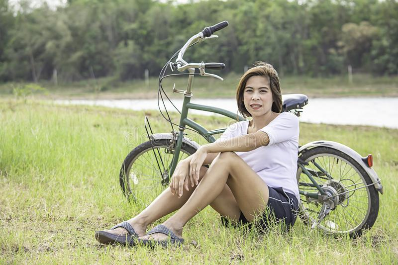 Asian woman sitting on the grass Background bicycle , water and trees.  royalty free stock images
