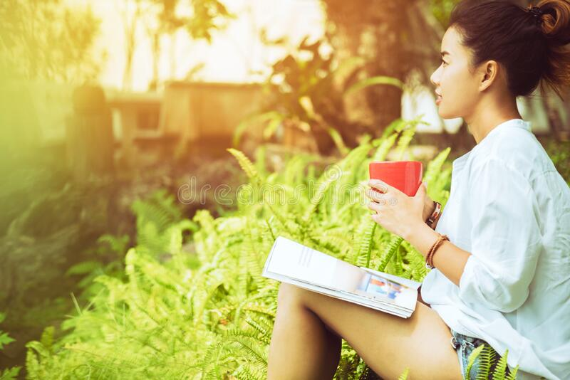 Asian woman Sitting relax. Read magazines and drink coffee. in the garden stock photo