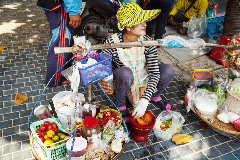 Asian woman sitting on a sidewalk, cooking and selling traditional Thai meal. Street food vendor with baskets royalty free stock photo