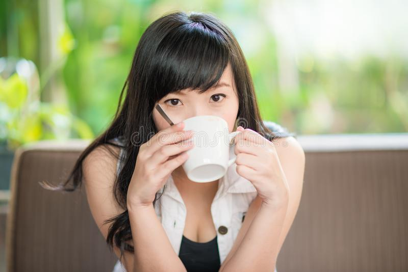 Asian woman sitting on sofa with coffee royalty free stock photography