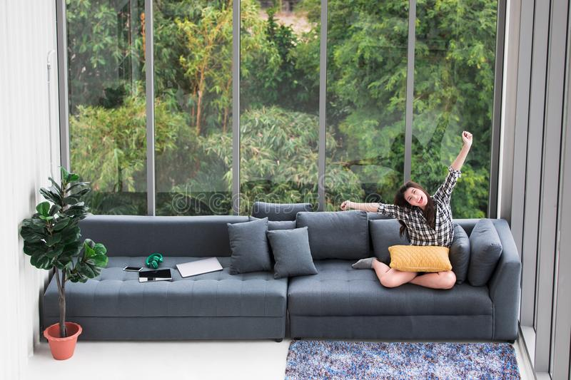 Asian woman sitting on sofa near big glass windows, relaxing alone in house with green forest in background. royalty free stock photography