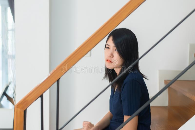 Asian woman sitting on stairs with depression of lonely have a headache,Mental disorder health care concept stock image