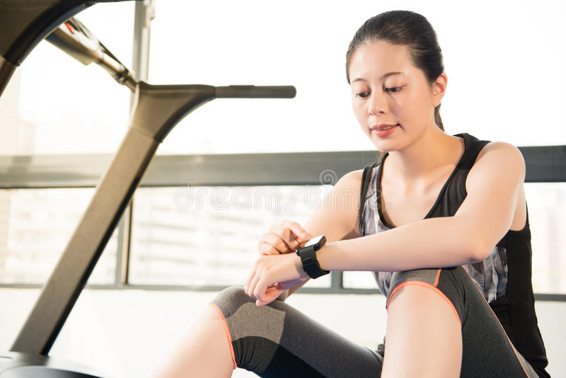 Asian woman sitting on treadmill. smartwatch check pulse rate. Asian woman rest sitting on treadmill use smartwatch check pulse rate. indoors gym background stock photos