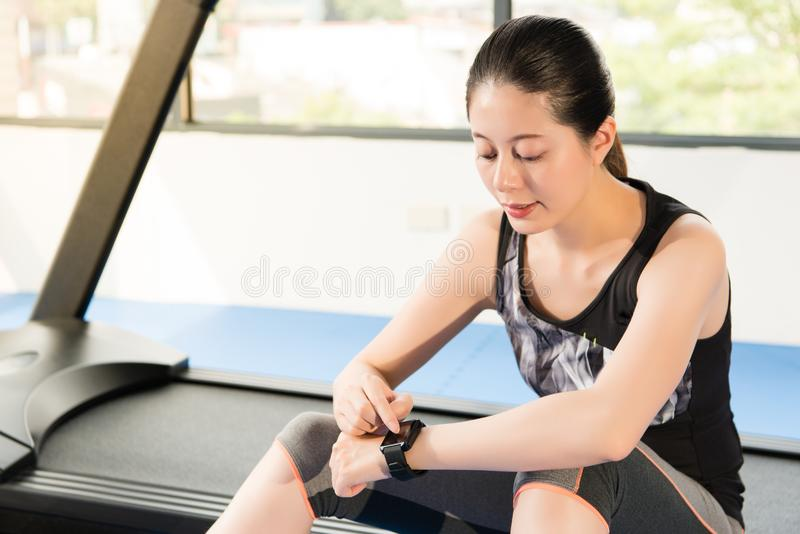 Asian woman sitting on treadmill. smartwatch check pulse rate. Asian woman rest sitting on treadmill use smartwatch check pulse rate. indoors gym background royalty free stock images