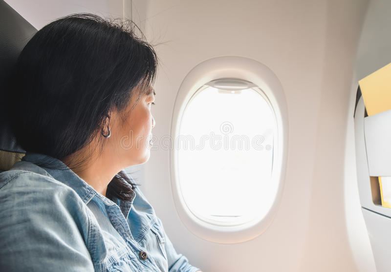 Asian Woman sitting at window seat in airplane and look outside stock photo