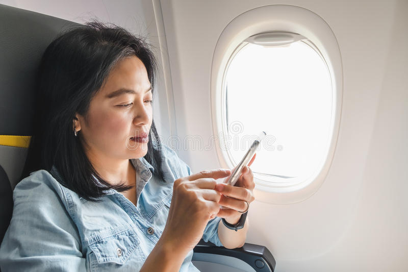 Asian Woman sitting at window seat in airplane and turn on airplane mode on mobile phone before take off stock image