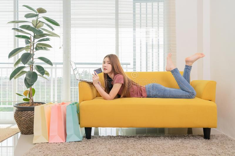 Asian woman sitting on the yellow sofa using laptop and cradit card shopping online near window and shopping bag. Young asian woman sitting on the yellow sofa stock photos
