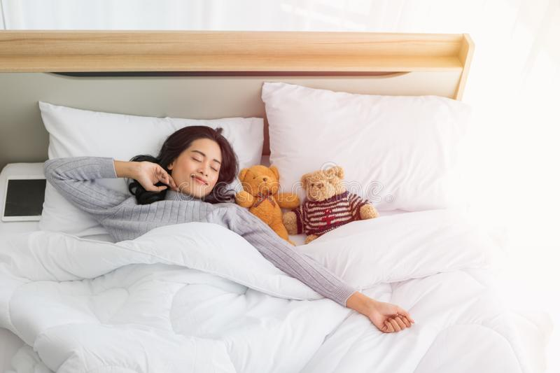 Asian woman sleeps on bed with two teddy bear stock photography