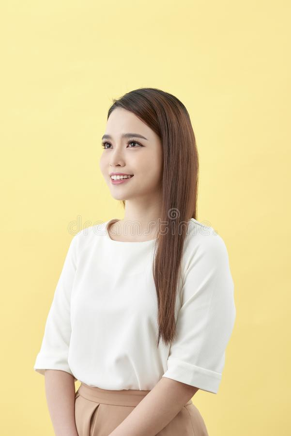 Asian woman smiling with dimple long hair black eyes on yellow background.  stock photography