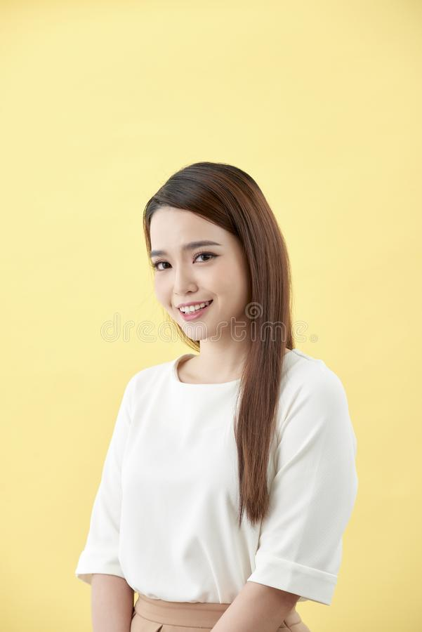 Asian woman smiling with dimple long hair black eyes on yellow background.  royalty free stock photography