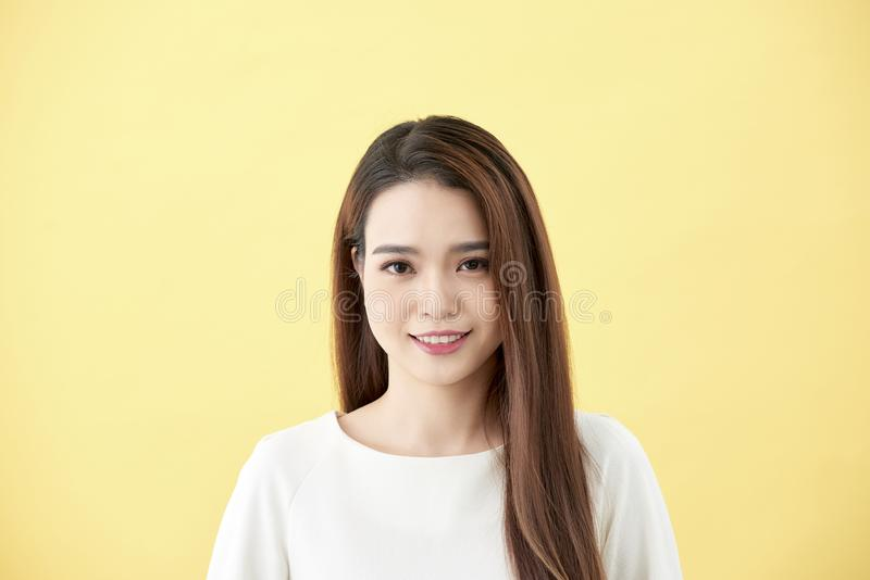 Asian woman smiling with dimple long hair black eyes on yellow background cute nice girl face vintage style Beautiful Asian girl. Oriental girl black hair long stock images