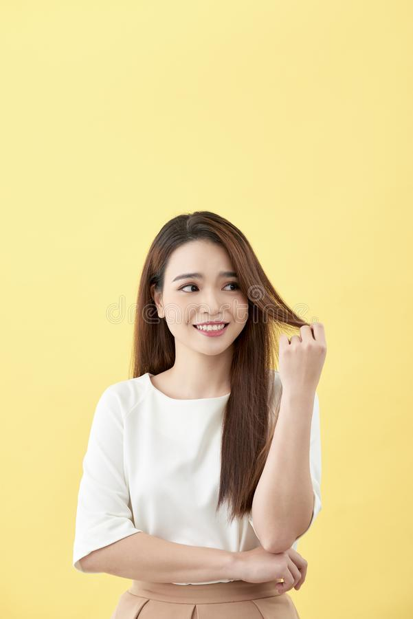 Asian woman smiling with dimple long hair black eyes on yellow background cute nice girl face vintage style Beautiful Asian girl. Oriental girl black hair long royalty free stock photo