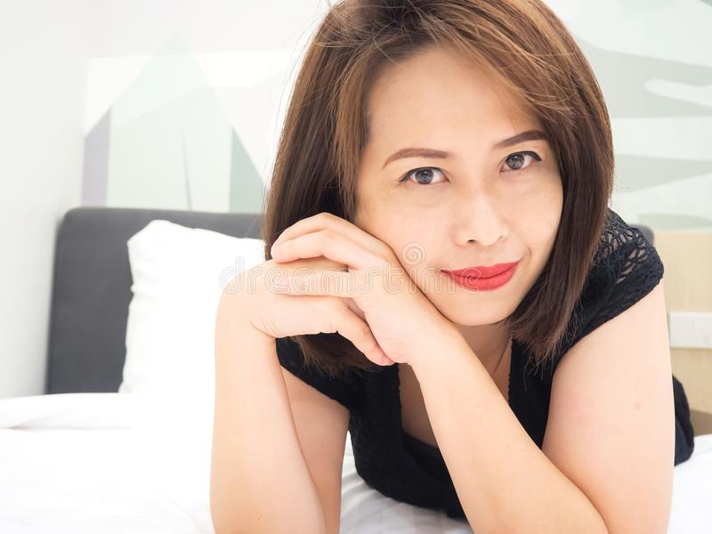 Asian woman smiling. Portrait woman laying down on bed. royalty free stock images