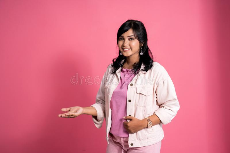Asian woman smiling and presenting copyspace stock photo