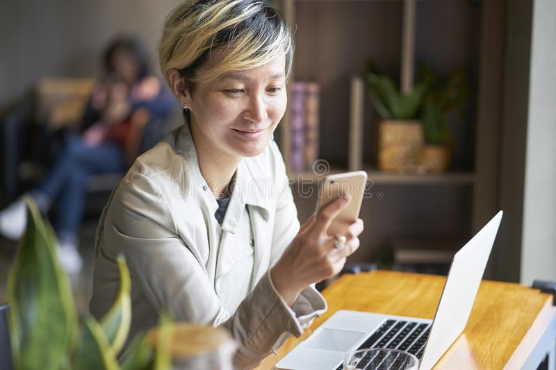Young Asian woman smiling using smart phone and laptop at coffee shop royalty free stock image