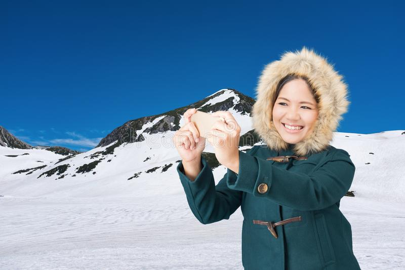 Asian woman on snow mountain. Asian woman wearing green coat with fur hat on snow mountain stock photo
