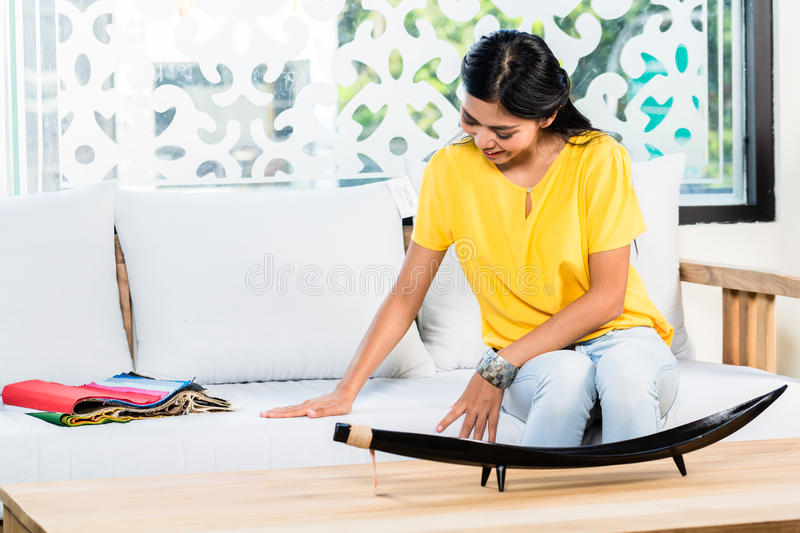 Asian woman on sofa couch in furniture store. Asian Indonesian woman sitting on sofa couch in furniture store showroom with color and material catalog royalty free stock image