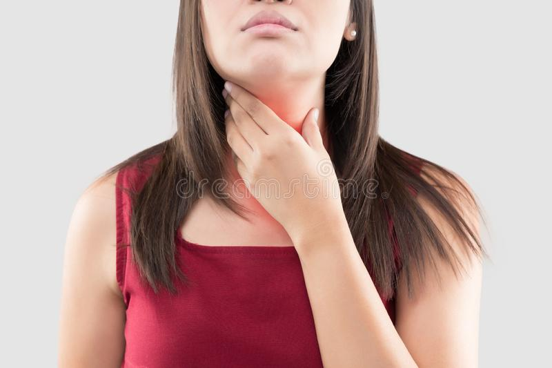Asian woman with a sore throat or thyroid gland against the gray background. Acid reflux or Heartburn. royalty free stock photos
