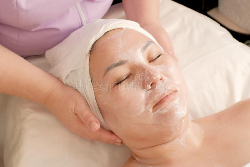 Asian woman on Spa treatments at the beauty salon. Healthy facial massage. Beautician causes cosmetic cream woman`s face. The. Asian woman on Spa treatments at stock photos
