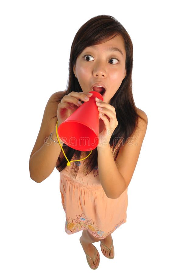 Asian Woman speaking through a red cone. Beautiful young Asian Woman picture taken from the top to give a big doll head effect royalty free stock image