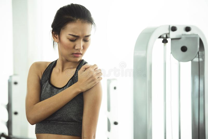 Asian woman in sportswear having shoulder pain royalty free stock photo