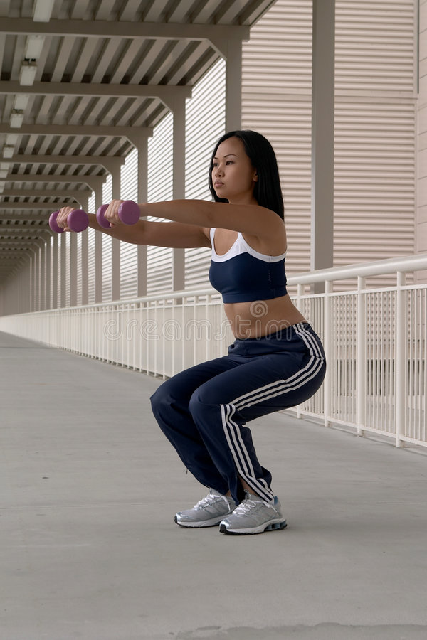 Asian Woman Squatting with Dumbbells stock photos