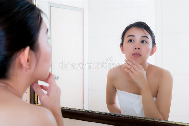 Asian woman squeezing pimples on her face while looking at reflection in mirror. royalty free stock photo