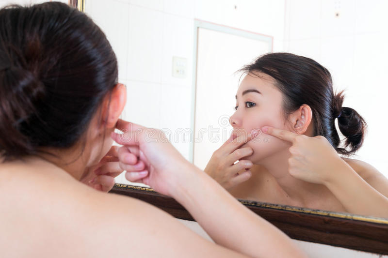 Asian woman squeezing pimples on her face while looking at reflection in mirror. stock photography