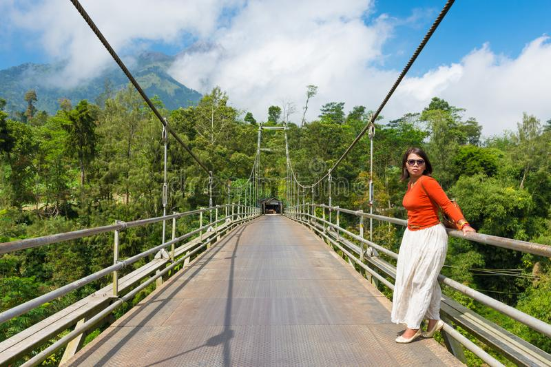 Asian woman standing on bridge looking around at scenic view in mountain region of java Indonesia royalty free stock images
